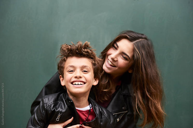 Mother and child laughing together against of green background by Guille Faingold for Stocksy United