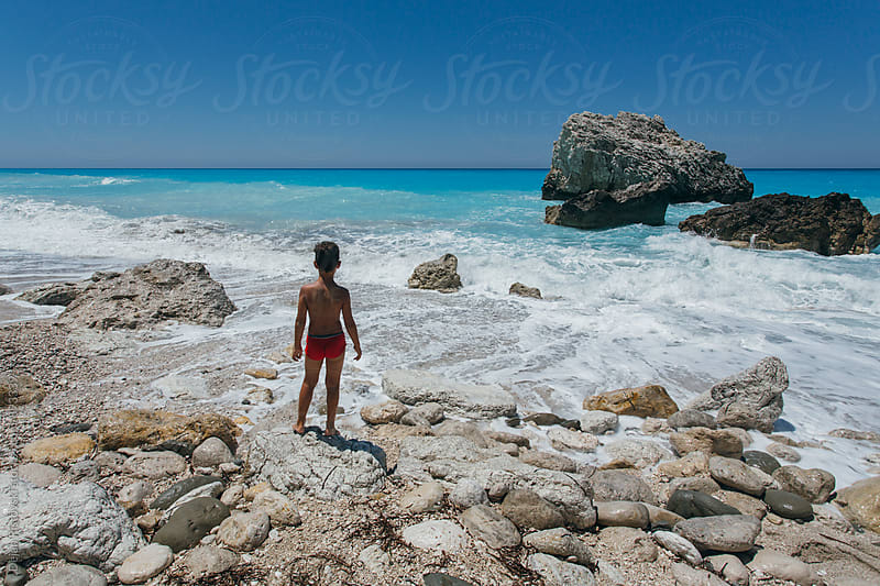 Boy on a beautiful natural beach. by Dejan Ristovski for Stocksy United