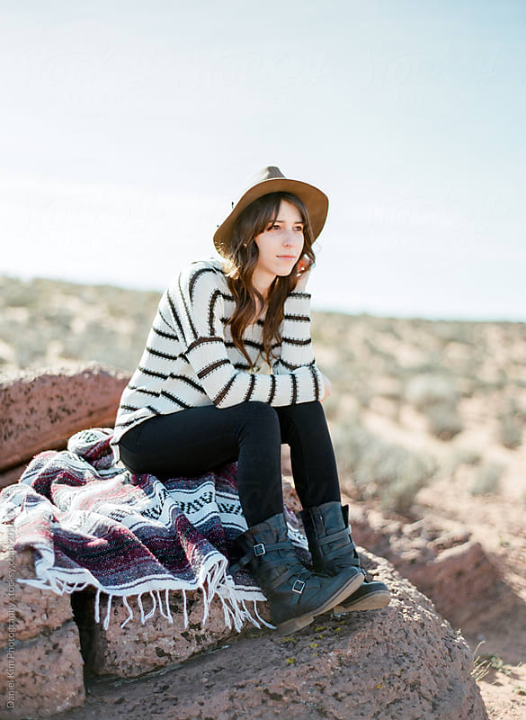 young woman sitting on rock in desert by Daniel Kim Photography for Stocksy United