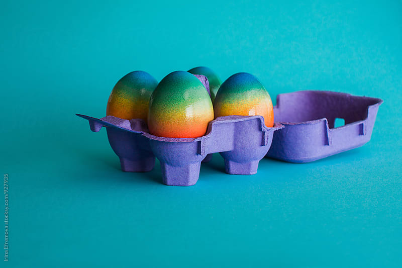 Rainbow colored eggs in a purple box  by Irina Efremova for Stocksy United