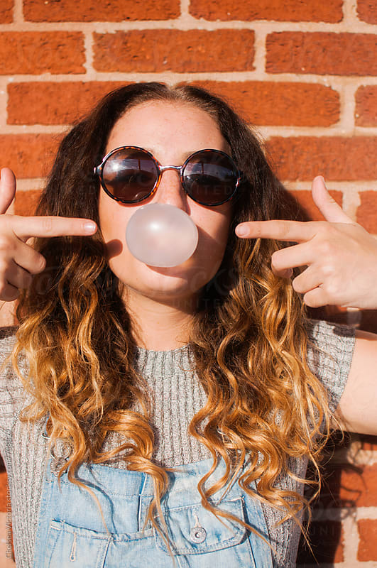 A young woman blowing bubble gum by Chelsea Victoria for Stocksy United