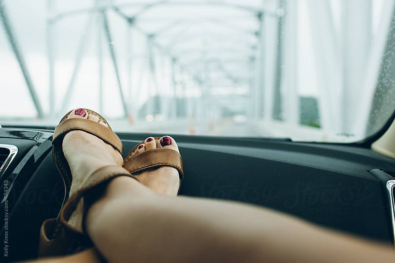 woman with feet on the dash during a summer road trip  by Kelly Knox for Stocksy United