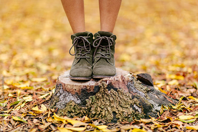 A woman wearing green suede boots and standing on a tree trunk by Kristen Curette Hines for Stocksy United