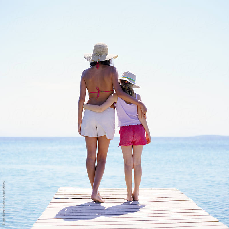 Mother and Daughter standing together on jetty by the sea. by Hugh Sitton for Stocksy United