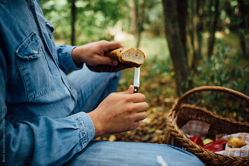 Man cutting bread on slices in the forest by Boris Jovanovic for Stocksy United