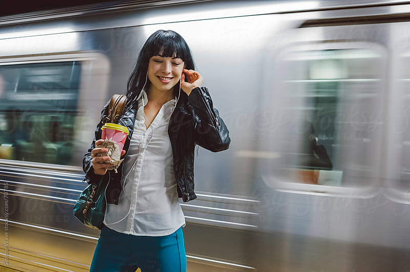 Happy woman standing against a subway train by GIC for Stocksy United