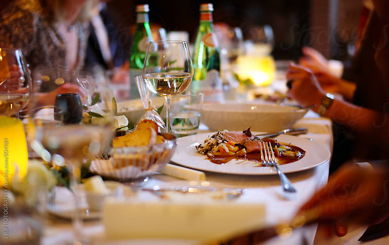 People dining at banquet table by J.R. PHOTOGRAPHY for Stocksy United