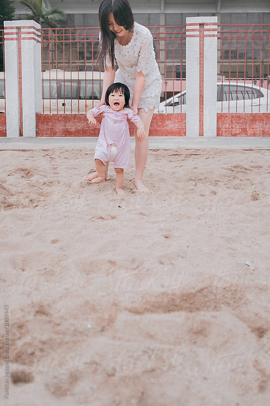 Asian baby girl learning walking by Pansfun Images for Stocksy United