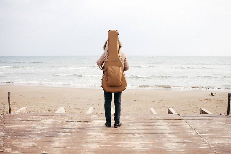Woman on the beach with a guitar by Giada Canu for Stocksy United