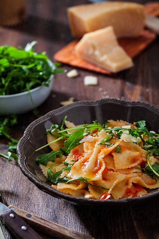 Pasta with tomato sauce and rocket salad by Davide Illini for Stocksy United