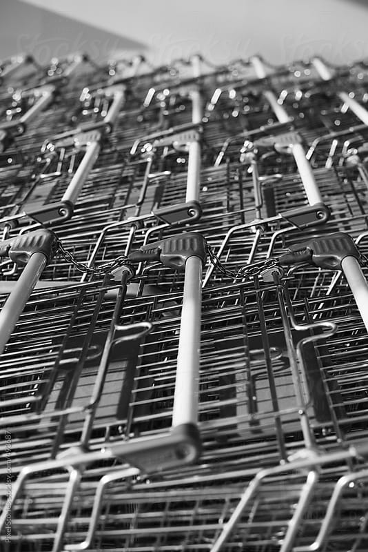 Row of empty shopping carts by Pixel Stories for Stocksy United