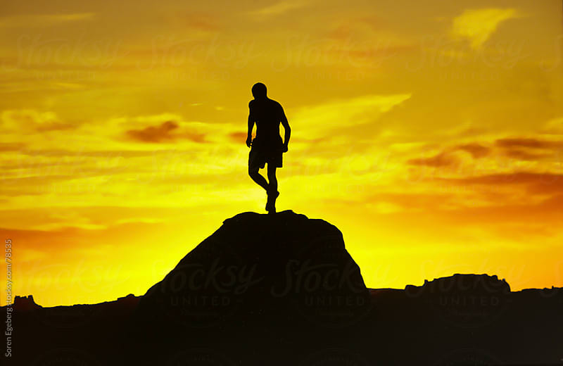 Mountain sunset with runner in silhouette on top of hill by Soren Egeberg for Stocksy United