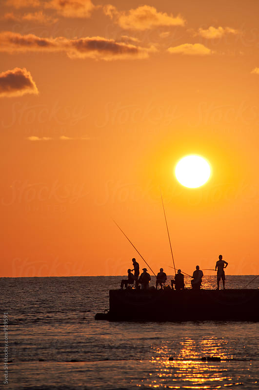 Sunset. Silhouettes of  fishermen. by Svetlana Shchemeleva for Stocksy United