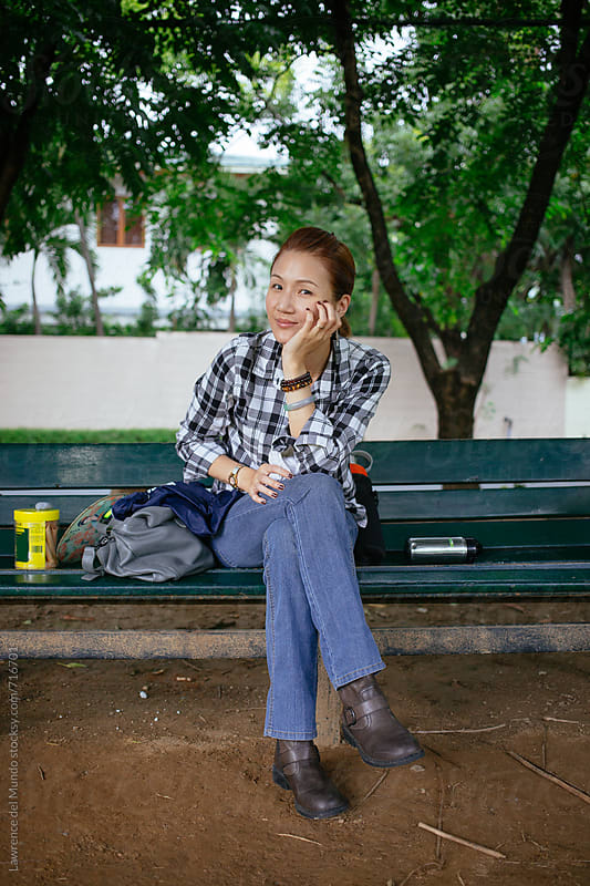 Young mommy looks at camera while sitting on a park bench while waiting for her sons.  by Lawrence del Mundo for Stocksy United