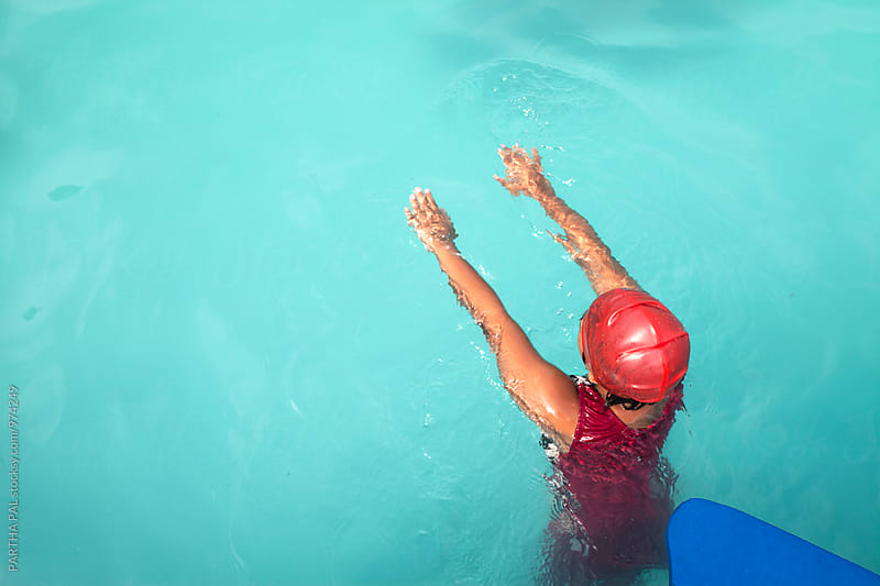 Teenage girl swimming in a pool by PARTHA PAL for Stocksy United