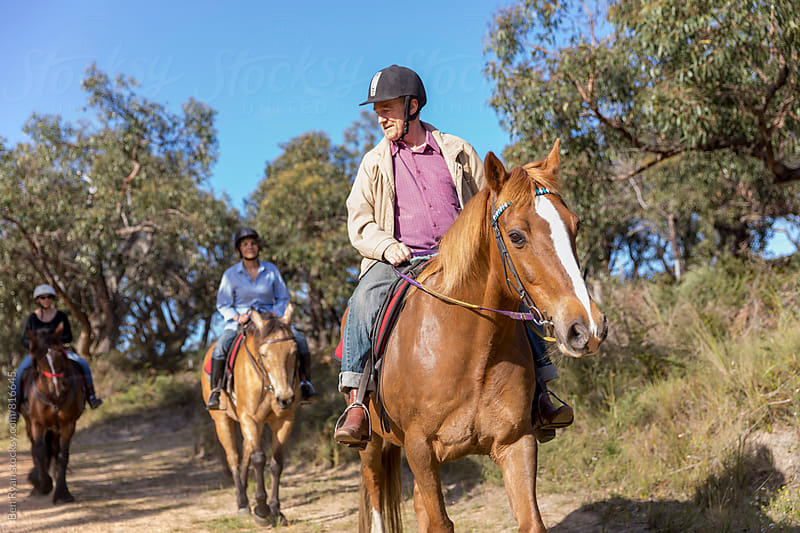 Group of horse riders let by senior male on tan horse with white face by Ben Ryan for Stocksy United