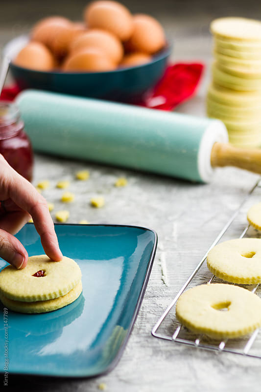 Woman pressing biscuit top onto jammie dodger by Kirsty Begg for Stocksy United