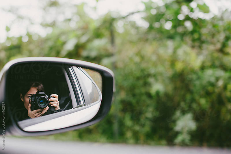 Woman taking a photograph of herself and landscape while riding in passenger seat of car by Lauren Naefe for Stocksy United