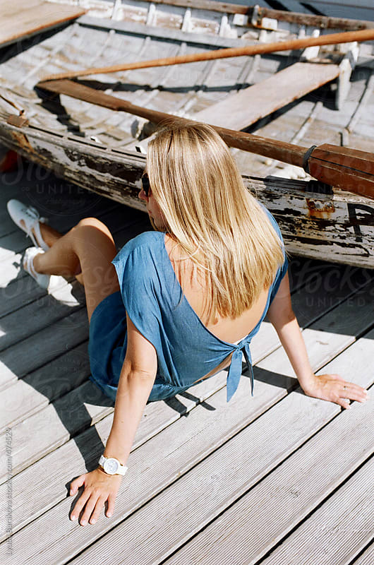 Back view of the young woman sitting on the board-floor near wooden boat  by Lyuba Burakova for Stocksy United