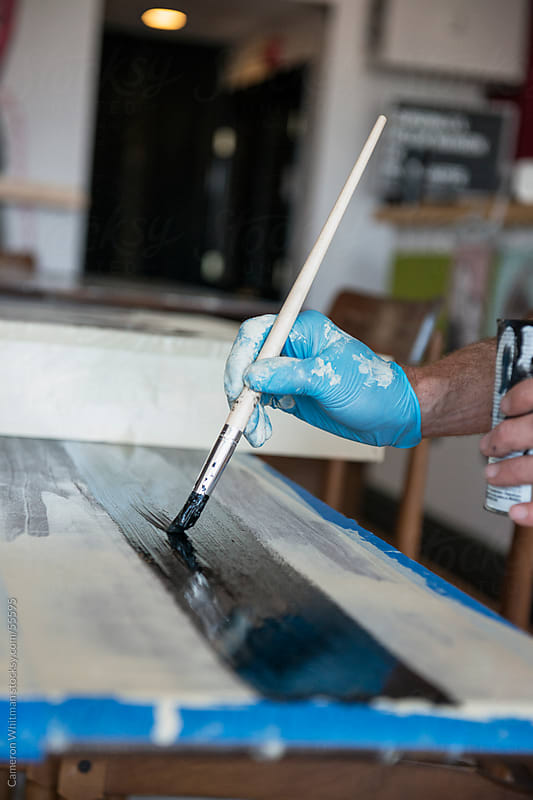 Close up of a paint brush in use by Cameron Whitman for Stocksy United