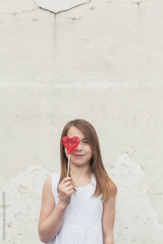 Little girl in white dress holding a red candy heart lollipop by Cindy Prins for Stocksy United