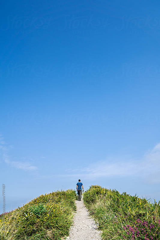 Young man walking toward the top of the mountain by ACALU Studio for Stocksy United