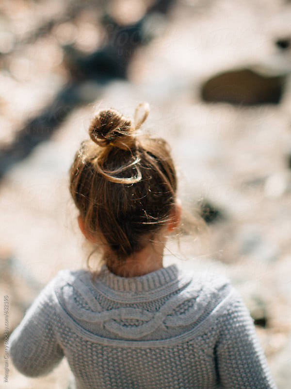 little girl walking with a topknot by Meaghan Curry for Stocksy United