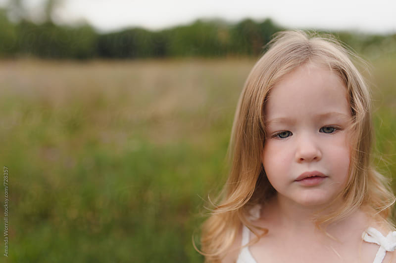 Portrait of a beautiful, young girl in nature, looking down by Amanda Worrall for Stocksy United