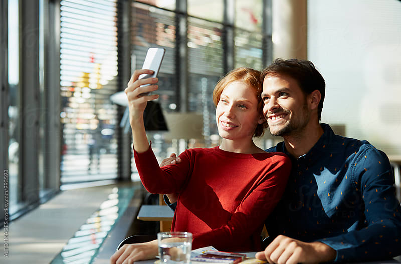 Happy Couple Making A Selfie In Restaurant by ALTO IMAGES for Stocksy United