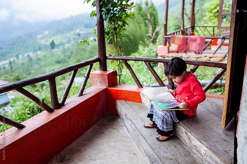 Little girl reading a story book sitting on the balcony by Saptak Ganguly for Stocksy United