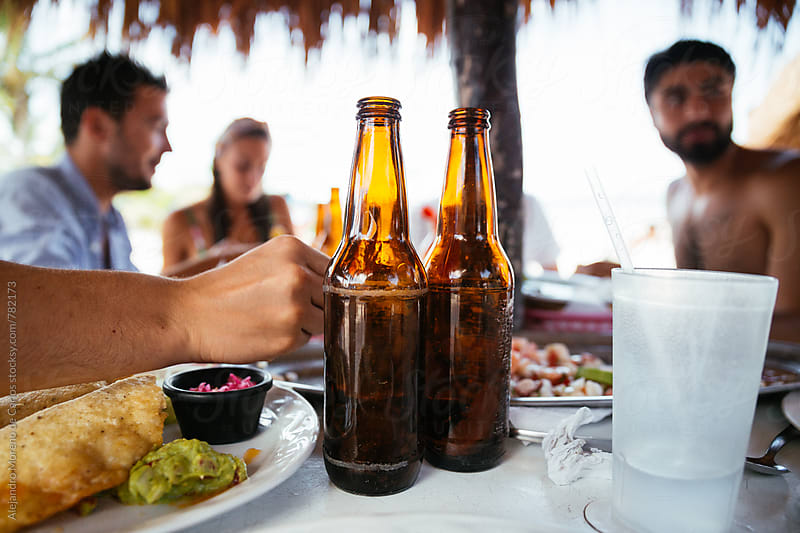 Front view of two beer bottles on a table surrounded by food at a beach bar by Alejandro Moreno de Carlos for Stocksy United