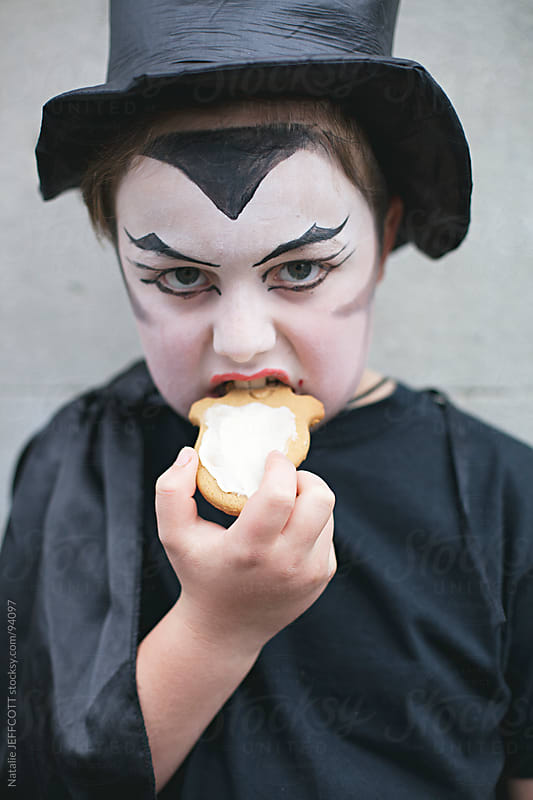 close up of boy dressed as a vampire for Halloween eating a treat by Natalie JEFFCOTT for Stocksy United