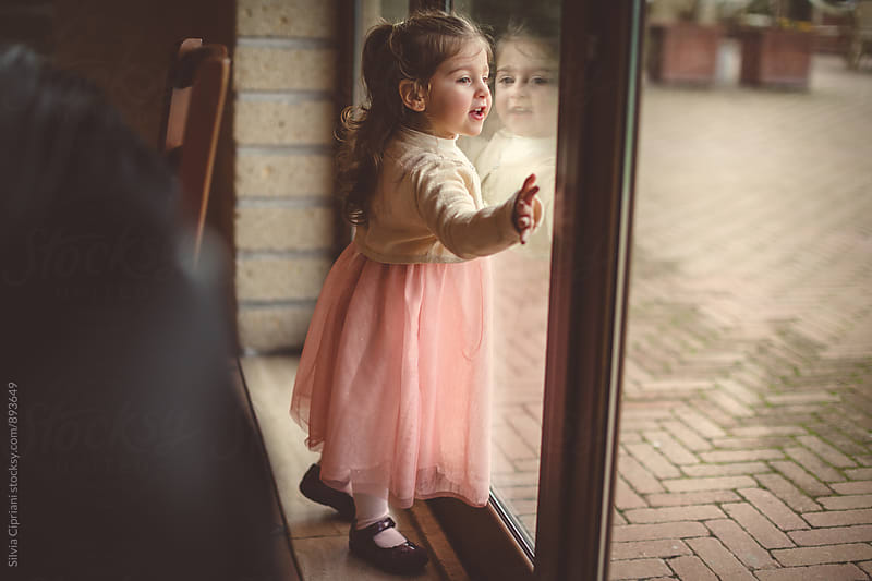 Little girl looking through a french door by Silvia Cipriani for Stocksy United