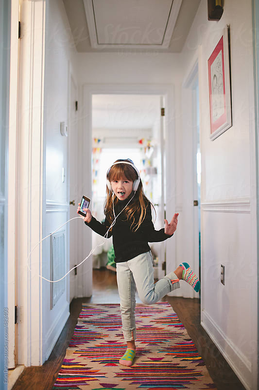 girl dancing in hallway with headphones on holding a device by Erin Drago for Stocksy United