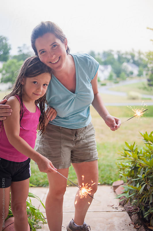 Little girl and mother with lit sparklers on July 4th by Brian McEntire for Stocksy United