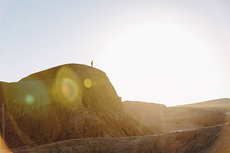 Silhouette Of A Person Standing On A Cliff At Sunset by Laura Austin for Stocksy United