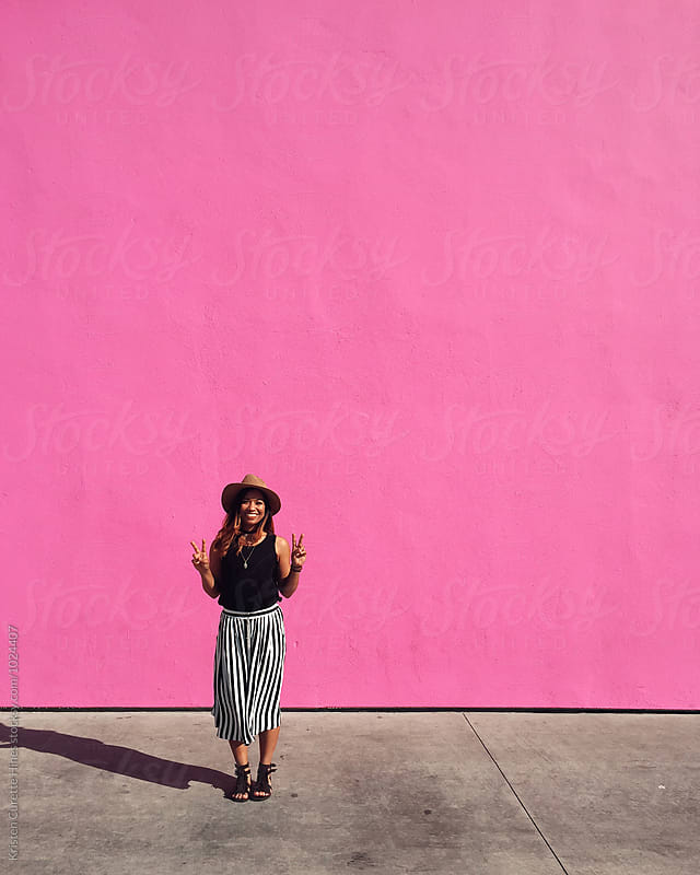 A young woman standing by a hot pink wall holding up the peace sign with both hands by Kristen Curette Hines for Stocksy United