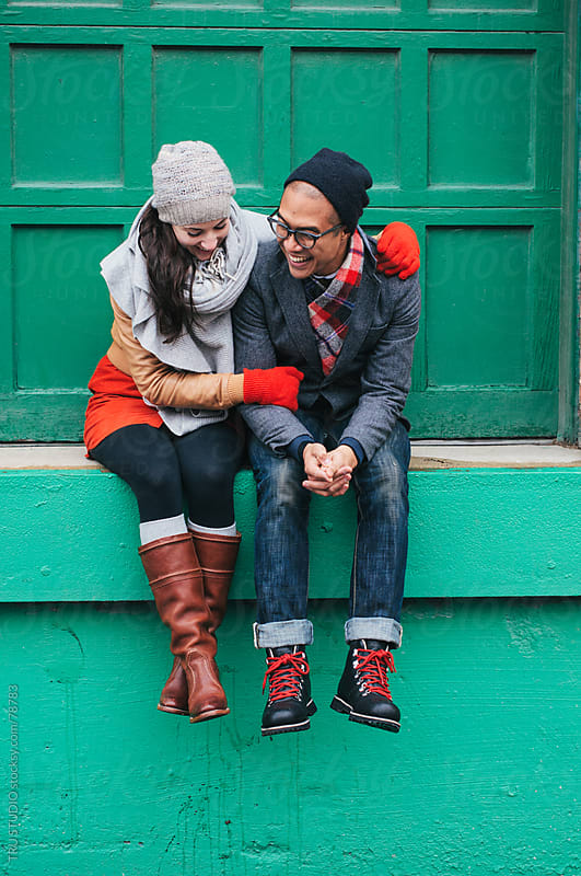 Young stylish couple in love snuggle and smile wearing hats and scarves sitting on green background by TRU STUDIO for Stocksy United