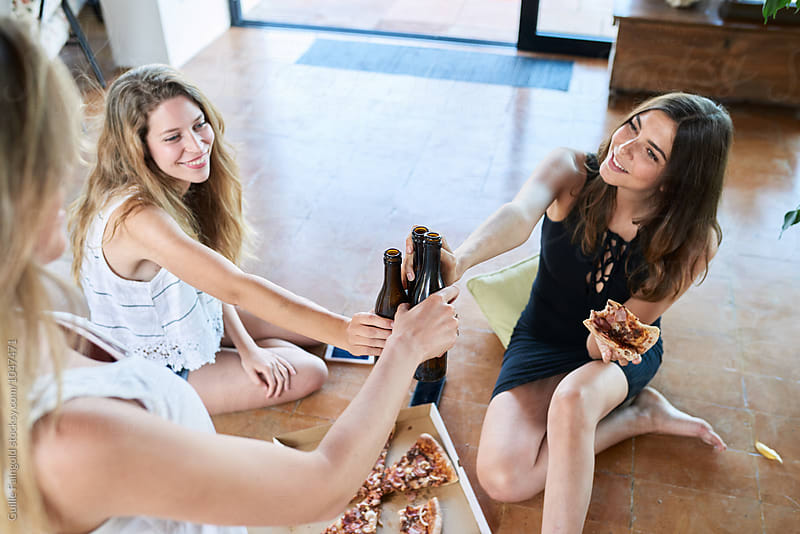 Cheerful girlfriends cheering with beer and pizza at home by Guille Faingold for Stocksy United