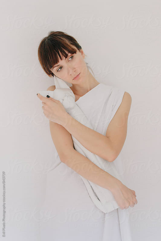 Portrait of a young female model with wooden white cat figure by Evil Pixels Photography for Stocksy United