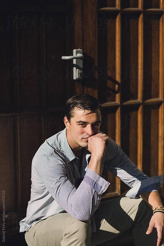 Portrait of a young man sitting on a sidewalk in the autumn sun by Gabriel Tichy for Stocksy United