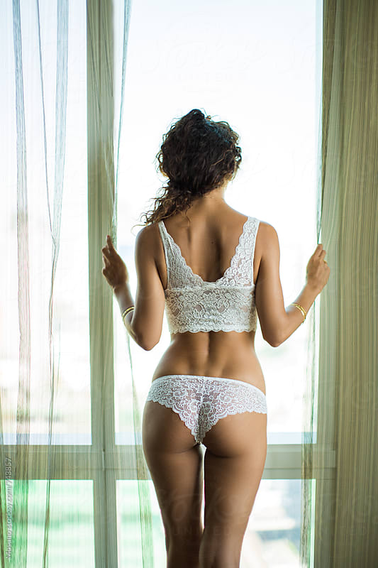 Woman in White Lingerie Standing by the Window by Mosuno for Stocksy United