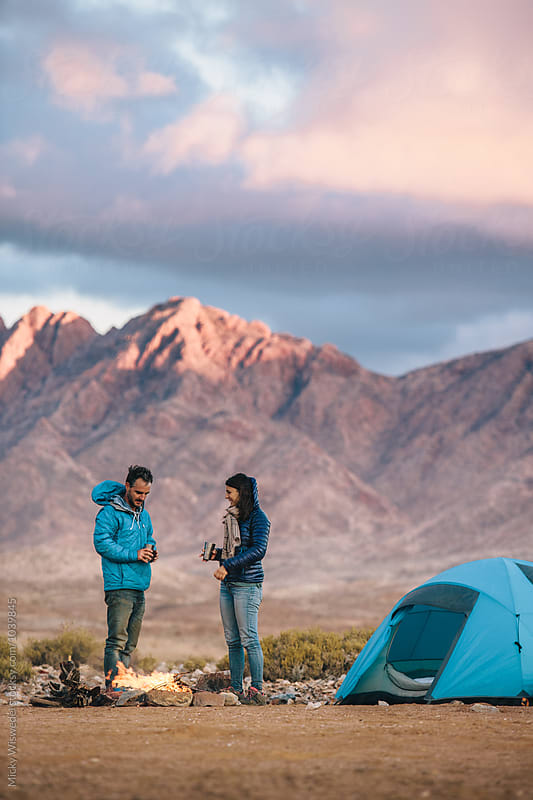 Outdoorsy hiking couple at their camp fire in a rugged mountain landscape by Micky Wiswedel for Stocksy United