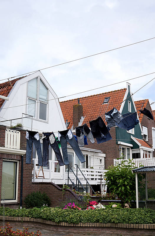 Laundry line with clothes in Dutch town by Marcel for Stocksy United