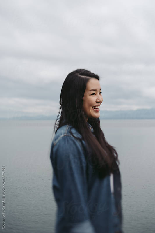 Young, beautiful asian woman smiling near ocean water by Rob and Julia Campbell for Stocksy United