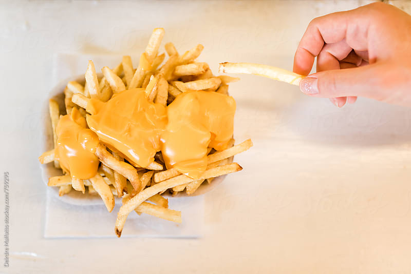 cheese fries with a hand removing one from the basket by Deirdre Malfatto for Stocksy United