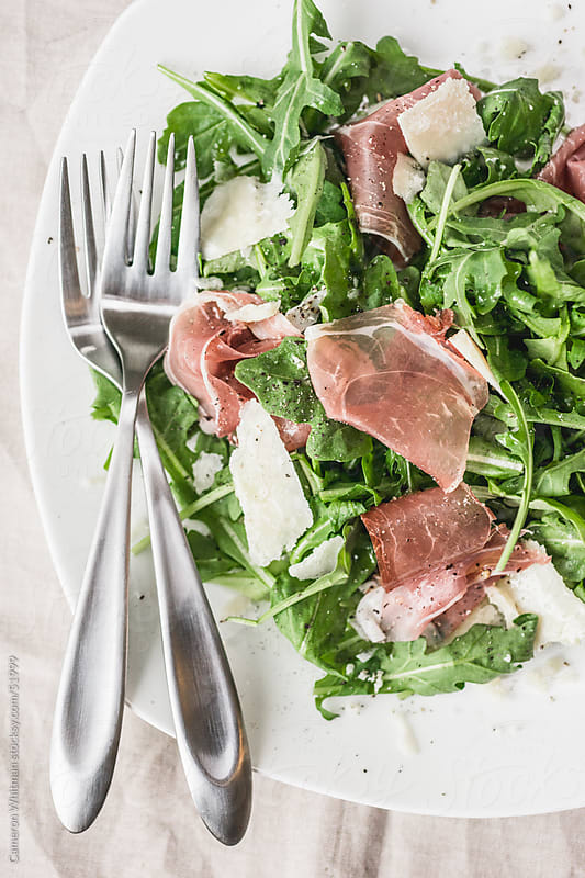 Arugula salad with Prosciutto and Parmesan cheese  by Cameron Whitman for Stocksy United