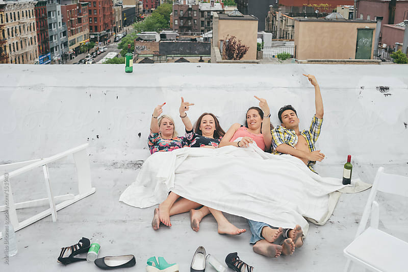 Friends Flipping the Bird while Smoking and Drinking on a New York City rooftop by Joselito Briones for Stocksy United