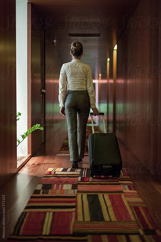 Businesswoman Walking Down the Hotel Hallway by Mosuno for Stocksy United