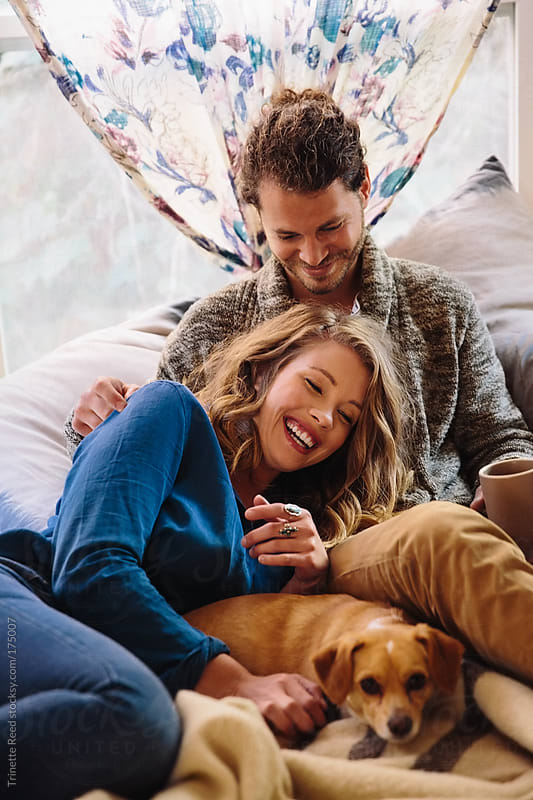 Couple relaxing on bed with their dog by Trinette Reed for Stocksy United